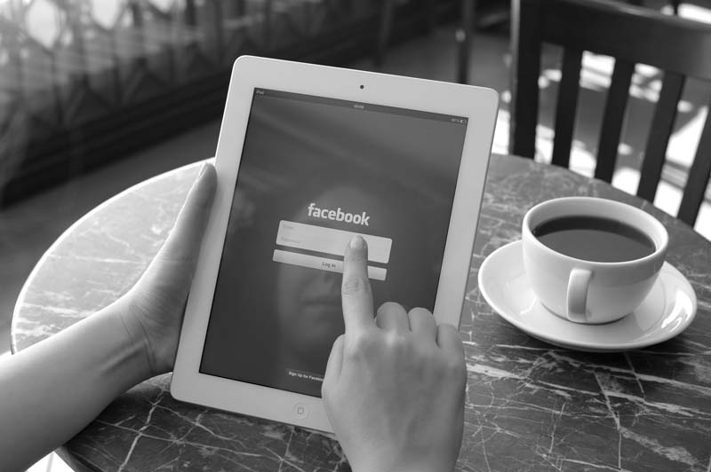 Facebook On An iPad Screen and a cup of coffee